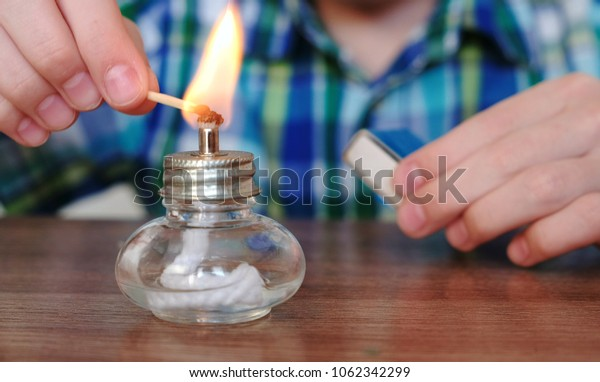 Experiments on chemistry at home. Closeup Boy's hands sets the burning alcohol lamp on fire with a match.