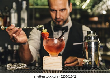 Expert barman is making cocktail at night club