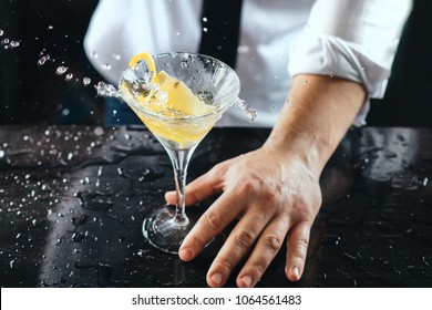 Expert barman making cocktail at nightclub. Bartender preparing cocktail at the bar. Preparing of martini cocktail. Nightlife club scene. Martini glass splash. Mixing alcoholic drinks.
