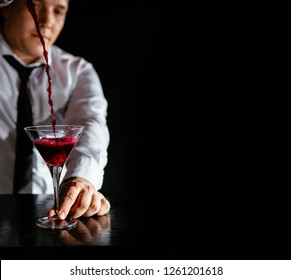 Expert barman making cocktail at nightclub.  Bartender preparing dark red cocktail at cocktail glass at the bar. Preparing of cosmopolitan cocktail. Red alcoholic drink ob black background.
