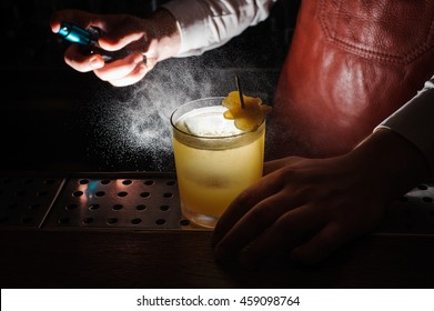 Expert barman is spraying on cocktail