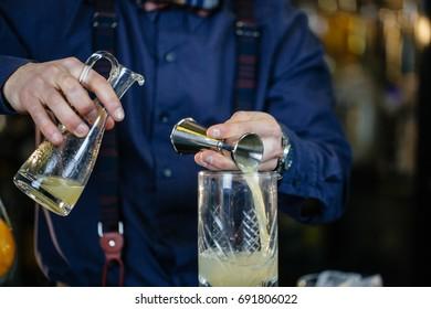 Expert Bartender is making cocktail at bar.