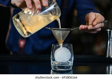 Expert Bartender is making cocktail at bar.