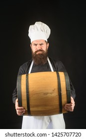 Expert brewer in apron holds barrel of beer. Qualitative of brewed drink at brewery factory. Brewer in apron&hat holds barrel with craft beer at brewery factory. Manufacturer carrying keg in brewery.