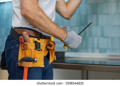 Expert. Cropped shot of young repairman, professional plumber holding a screwdriver while fixing a sink in the kitchen indoors