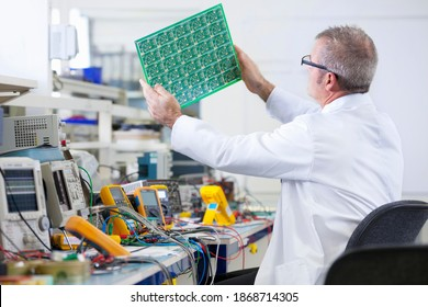 An expert engineer in a lab coat examining the printed circuit board at an electrical test bench