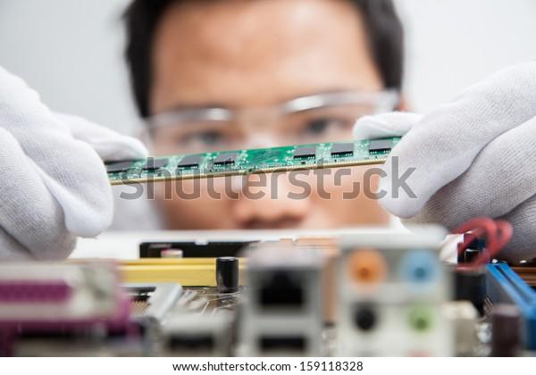 Expert engineers examining computer equipment.