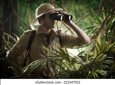 Expert explorer in the jungle looking away through binoculars.