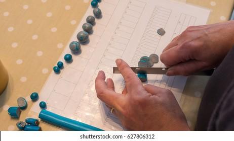 Expert female hand making jewlery from polymer clay. Hobby, handicraft