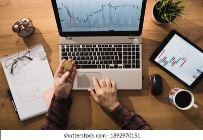 Expert man working while bitcoin is standing on the table. man viewing monetary earnings graphs.