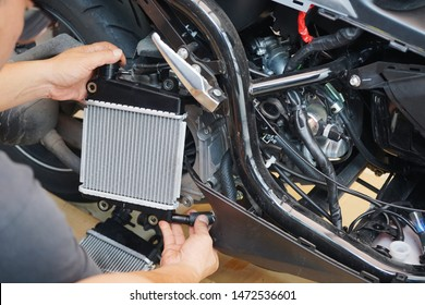 Expert technician install a radiator to motorcycle or scooter,The radiator is the main component of the cooling system and to keep the engine from overheating