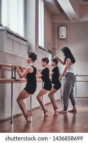 Expirienced ballet teacher is showing to young ballerinas how to do important exercises and correct them.