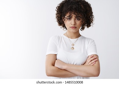 Explain yourself. Displeased angry young attractive girlfriend gloomy look camera disappointed cross arms chest defensive standing offended sulking stare camera assured assertive, white background
