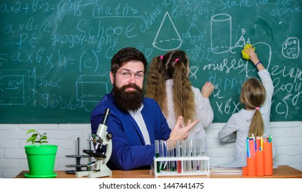 Explaining biology to children. How to interest children study. Fascinating biology lesson. School teacher of biology. Man bearded teacher work with microscope and test tubes in biology classroom.