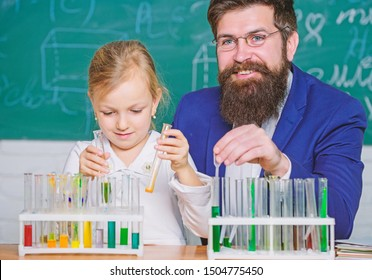 Explaining chemistry to kid. How to interest children study. Fascinating chemistry lesson. Man bearded teacher and pupil with test tubes in classroom. Private lesson. School chemistry experiment.