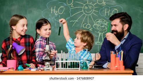Explaining chemistry to kids. Fascinating chemistry lesson. Man bearded teacher and pupils with test tubes in classroom. School chemistry lab. Science involves theory. School chemistry experiment.