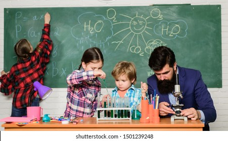 Explaining chemistry to kids. Fascinating chemistry lesson. Man bearded teacher and pupils with test tubes in classroom. Observe reaction. Science is always the solution. School chemistry experiment.