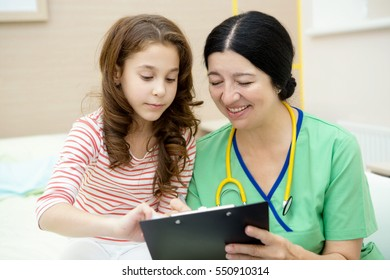 Explaining results. Senior female pediatrician smiling happily while explaining something to her young patient during checkup hospital childhood profession work job clinic people medicine concept