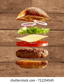 An exploded diagram view of a burger, with onion, lettuce, cheese, tomato and a toasted bun on a rustic timber background with copy space.