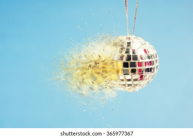 Exploding disco mirror ball on blue background. Concept of wild nightlife, extreme clubbing and hot crazy party.