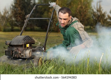 Exploit, old lawn mower in the cloud of exhaust fumes. Gardner trying to fix the failure.