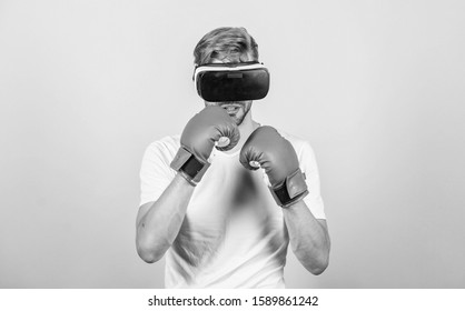 Explore cyber space. Cyber sport concept. Cyber coach online training. Cyber sportsman boxing gloves. Augmented 3D world. Man boxer virtual reality headset simulation. Man play game in VR glasses.
