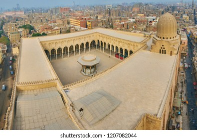 Explore medieval Sultan Al-Mu'ayyad mosque from the tower of Bab Zuwayla Gate, that opens the view on the zigzag shaped dome, foursquare roof and ablution fountain in mosque's courtyard, Cairo, Egypt.
