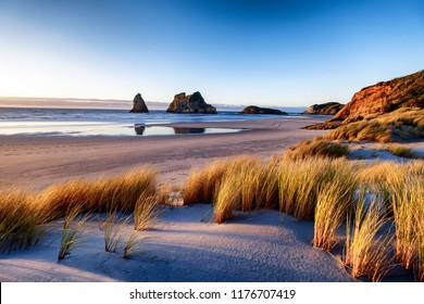 Explore the wild and rugged northern most point of the South Island, New Zealand. Wharariki Beach is a beautiful tourist attraction and destination. The image is peaceful, breathtaking and amazing.