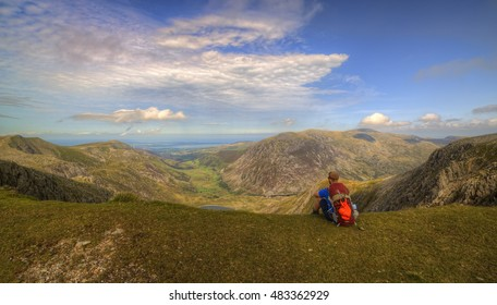 An explorer explores the Gylder Fach high up on Snowdonia moutain range in Wales. Emphasising exploration and traveling, backpacking and hiking in the outdoor world.