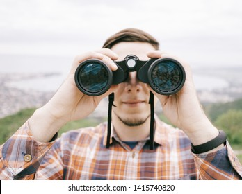 Explorer hiker young man in plaid shirt looking through binoculars on background of summer mountains and sea bay outdoor, front view. Travel concept.