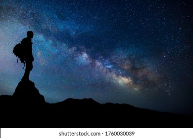 Explorer or man doing night trekking with the milky way on background. Man silhouette doing trekking and looking the stars. Elements of this image furnished by NASA.
