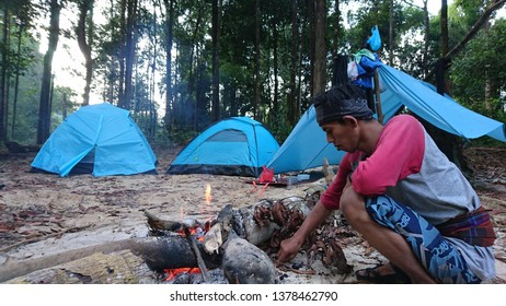 An explorer is setting the fireplace around the tent, West Borneo, Indonesia - March 07 2019