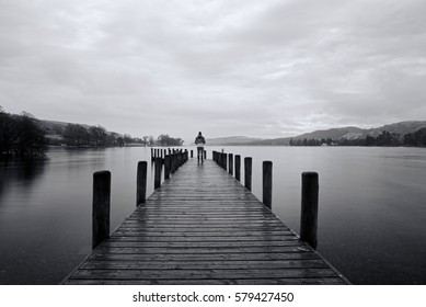 an explorer stands at the end of a jetty at Coniston water on the lake district in the UK