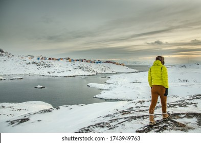Explorer walking around hilly rocks on a western coastline of arctic Greenland with a view of small bay and panorama on Inuit settlement with colorful houses in suburn of small town Sisimiut