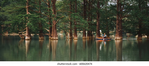Explorer young man kayaking on lake on background of beautiful cypresses in summer, Anapa, Russia.