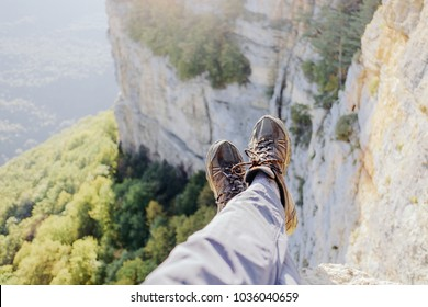 Explorer young man sitting on edge of cliff over valley, view of legs, pov.