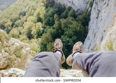 Explorer young man sitting on edge of cliff over valley, point of view.