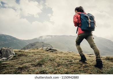 Explorer young woman with backpack going up on mountain outdoor.