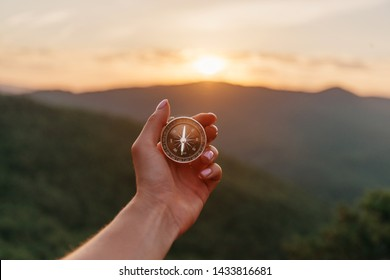 Explorer young woman holding compass in hand in summer mountains at sunrise, point of view. Concept of hiking and travel.