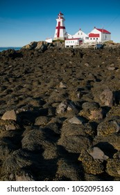 Exploring Head Harbor lighthouse in Canada involves climbing over rocks covered in seaweed during low tide.