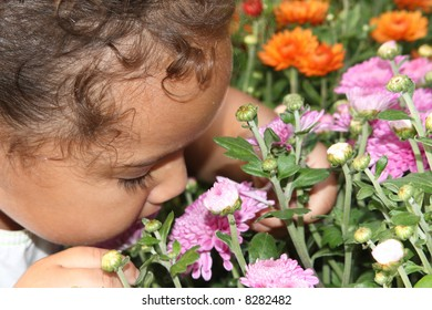 exploring her world by smelling the flowers