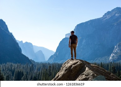 Exploring Nature - Hiker Stands On Top of Mountain looking out at Yosemite National Park