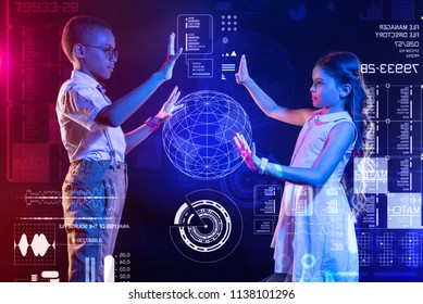 Exploring new devices. Clever progressive schoolchildren standing opposite each other and looking interested while making a realistic hologram of the Earth