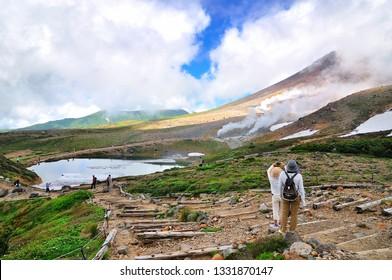 Exploring on trail around the ropeway's upper station at Asahi-dake Mountain (Mt. Asahidake), Higashikawa, Highest Mountain in Hokkaido in early summer.