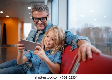 Exploring online together. Middle-aged father is sitting on airport bench with his little wonderful daughter. Child is holding modern smartphone and they are looking at screen of gadget with interest