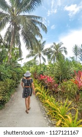 Exploring paradise - back of woman walking on path through lush exotic vegetation in Samoa, South Pacific
