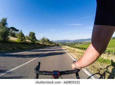 Exploring Tuscany on a racing bicycle. Young adult man riding a bicycle on the beautiful Chianti region countryside. POV