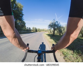 Exploring Tuscany on a racing bicycle. POV. Young adult man riding a racing bicycle on the wonderful Chianti region on a summer sunny afternoon.