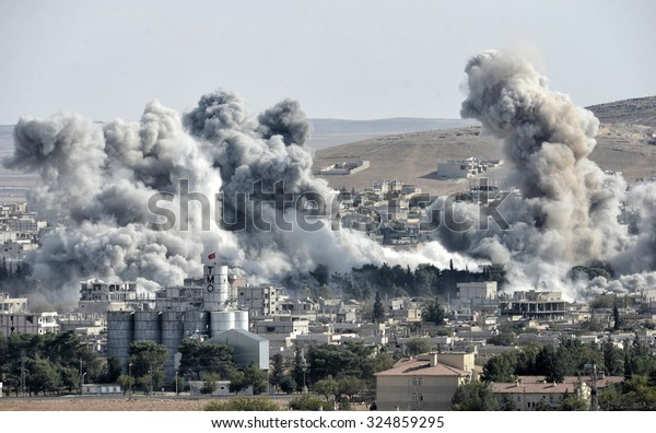 An explosion after an apparent US-led coalition airstrike on Kobane, Syria, as seen from the Turkish side of the border, near Suruc district, 18 October 2014, Turkey , Syria.
