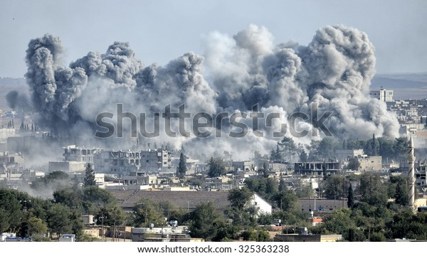 An explosion after an apparent US-led coalition airstrike on Kobane, Syria, as seen from the Turkish side of the border, near Suruc district, 24 October 2014, Sanliurfa, Turkey